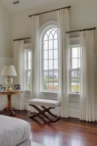 Arch window with drapery at varying heights